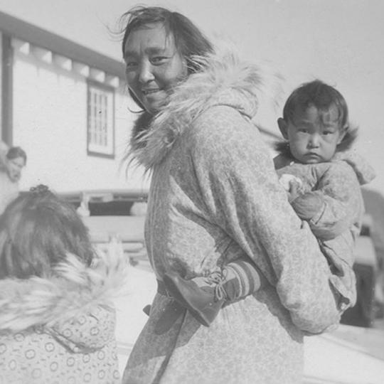 """Woman with children outside of post buildings at Tuktuk [Tuktoyaktuk]."" [193-?]. (Photographer: Unknown. HBCA-1987-363-E-140/1)"