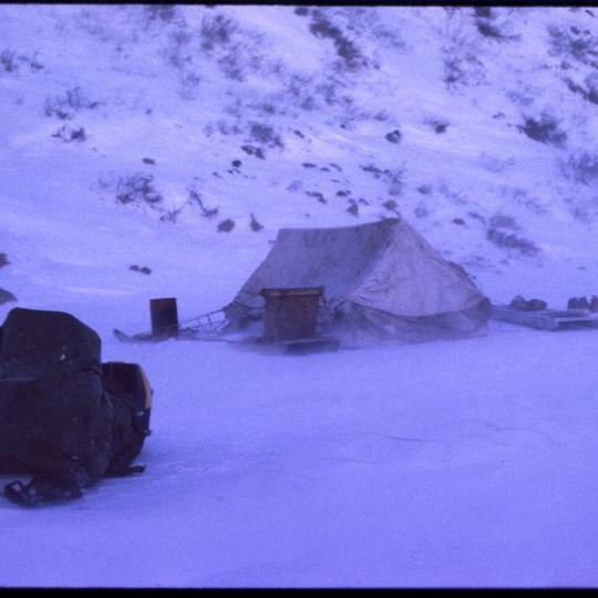 tent and skidoo camp in purple winter light