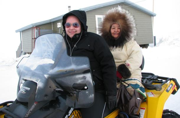 Two Paulatuk residents on the snowmobile.