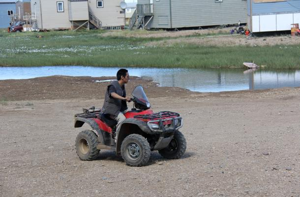 A Paulatuk resident drives on an ATV in the summer.