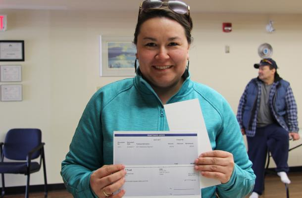 An Inuvialuit beneficiary collects a distribution payment cheque in Inuvik