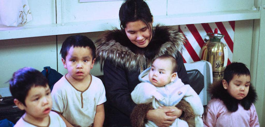 Bessie Kuptana sitting surrounded by four young children from Paulatuk.